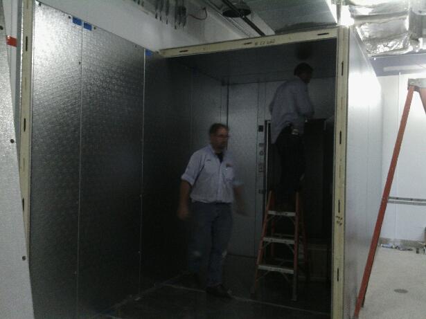 Installing walk in freezer ceiling.